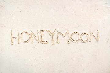"Handwriting words ""Honeymoon"" on sand"