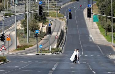 Jewish worshippers walk along an empty street in Jerusalem during the Jewish holiday of Yom Kippur