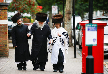Jewish people walk around the Stamford Hill during Yom Kippur, in London