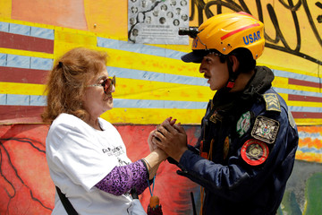A woman thanks a rescue worker after a minute of silence at the Tlalpan housing project, affected by the September 2017 earthquake, in Mexico City