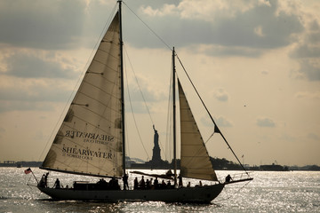 A sailboat passes by the Statue of Liberty in New York Harbor as seen from Battery Park in New York