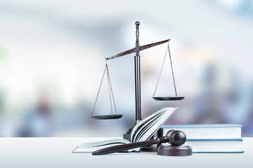 Justice Scales, books and gavel on dark