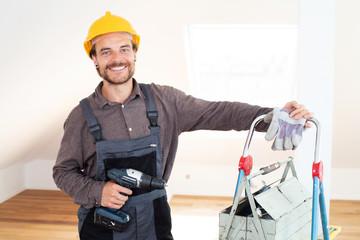 Handwerker lächelnd mit Werkzeug in einem modernen Wohnraum
