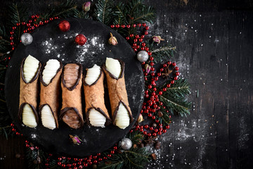 Traditional Sicilian cannoli with Christmas decoration on the wooden background with blank space,selective focus