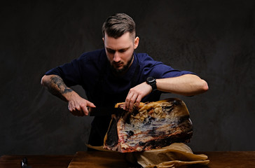 Focused chef cook cutting exclusive jerky meat on a table in a hunting house on dark background.