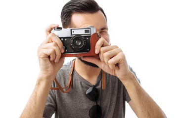 Portrait of a handsome photographer guy with a beard, taking pictures with a camera standing on a white background