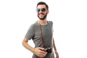 Portrait of a handsome hipster guy with glasses, with a camera, on a white background