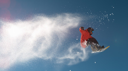 SLOW MOTION: Snowboarder jumping big air, snowflakes flying behind him in winter