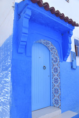 Vivid blue door in Middle Eastern style with geometric tiled framed entry and knocker with Spanish tiled overhang.