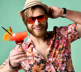 Young man in hat and sunglasses drinking margarita cocktail drink juice happy looking at camera laughing over light green
