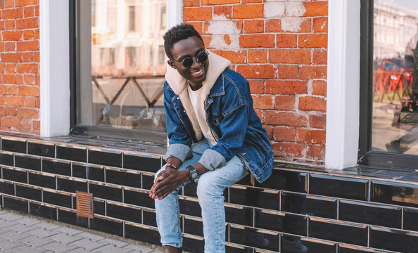 Fashion smiling african man wearing jeans jacket sits on city street, brick wall background