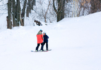 cute young boy in gray helmet and orange googles, in blue jacket snowboarding with instructor on white snow background. winter sport, active lifestyle concept.