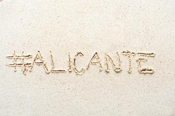 "Handwriting words ""Alicante"" on sand"