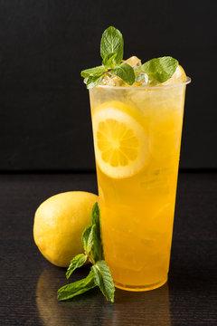 Iced lemonade with mint, lemon slices, and lemon on dark wood table