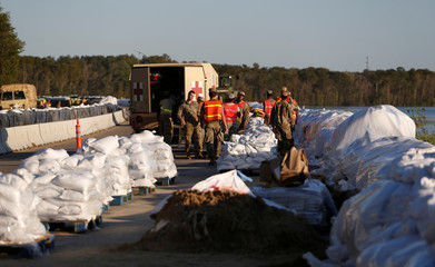 Members of the National Guard work on a long sand bag flood barrier being built by the South Carolina Department of Transportation on U.S. 501 to lesson damage to roads anticipated from floods caused by Hurricane Florence now downgraded to a tropical depre