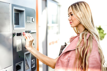 Stylish beautiful girl pays for purchases by credit card standing in the shopping center at the payment terminal