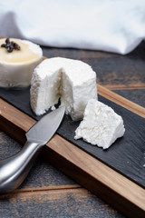 French soft cheeses, variety of different taste goat milk natural cheeses on granite plate close up sesrved as dessert