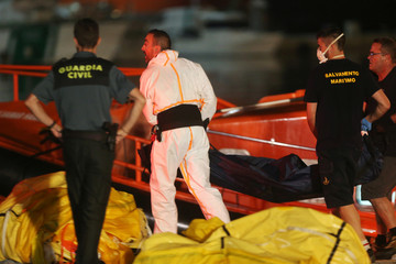 Rescuers carry a body bag with a dead migrant after arriving on a rescue boat at the port of Malaga