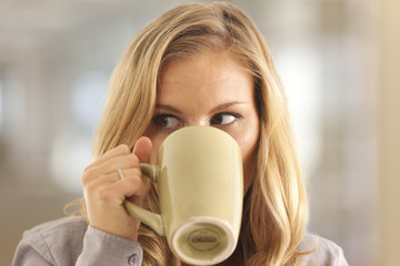 Close-up of woman drinking coffee inside office building
