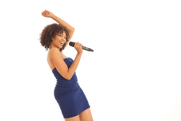 Young energetic woman singing and dancing with microphone isolated on white