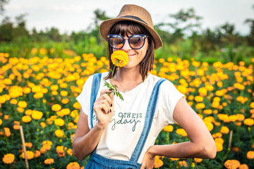 Close up portrait of happy and beautiful young woman relaxing enjoying the fresh beauty of gorgeous orange marigold flowers field in travel and holidays. Bali island.