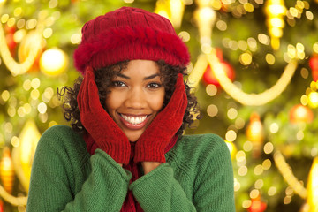 Close up portrait of joyful young woman in front of Christmas tree