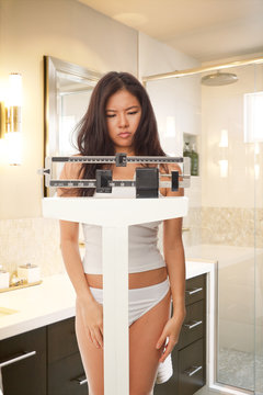 Disappointed young Asian woman standing on balance scale inside bathroom
