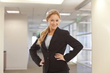 Portrait of young girl in business suit standing in office building