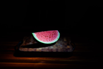 Big slice of watermelon on chopping board on dark background under spot light