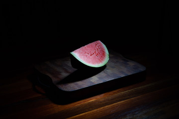 Watermelon slice on chopping board on black background with harsh light