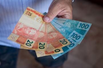 Hand holding brazilian money