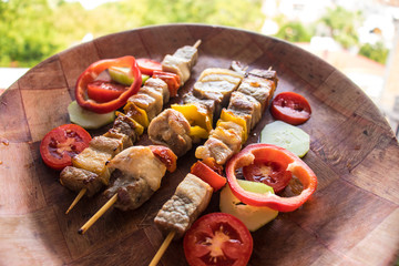 Skewered meat prepared on grill with vegetables. Barbecued shish kebab or shashlik on sticks