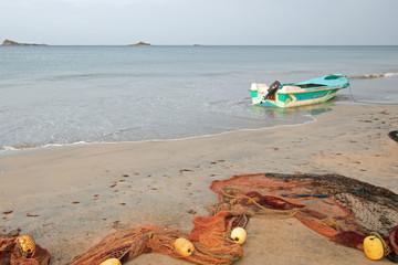 Small fishing boat and fishing nets on Nilaveli beach in Sri Lanka Asia
