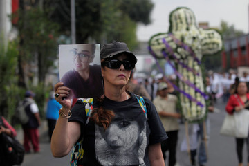 A woman carries a picture of a relative during a march by people with homes affected by the September 2017 earthquake to complain about the lack of government support, in Mexico City