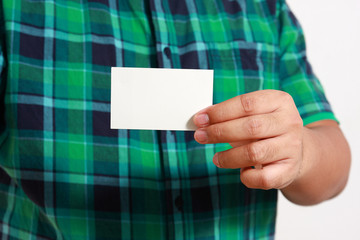 Working men in green shirt holding white business card with space for writing text.