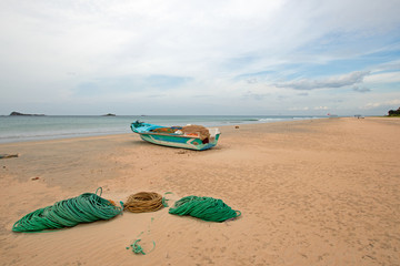 Small deep sea fishing boat next to ropes and nets on Nilaveli Beach in Trincomalee state in Sri Lanka Asia