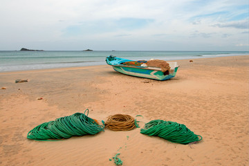 Deep sea fishing boat next to ropes and nets on Nilaveli Beach in Trincomalee state in Sri Lanka Asia