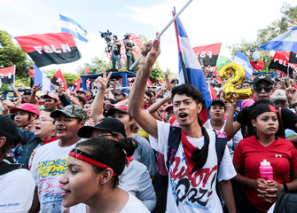 Supporters of Nicaraguan President Ortega shout slogans during a march in Managua
