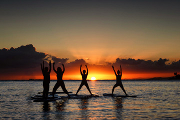 Silhouette of women doing yoga on stand up paddle boards at a golden hour sunset