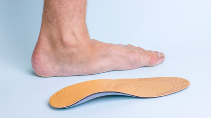 The left leg of an adult male with signs of foot disease next to the orthopedic insole. Means for the treatment of flat feet.