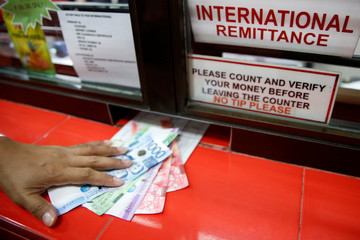 Philippine Peso bills sent by a Filipino working abroad are pictured being received by a relative at a money remittance center in Makati