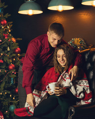 Loving couple celebrates Christmas. Guy stole his girlfriend with warm rug. Girl is holding cup with hot drink. Christmas tree in background. Happy Holidays.