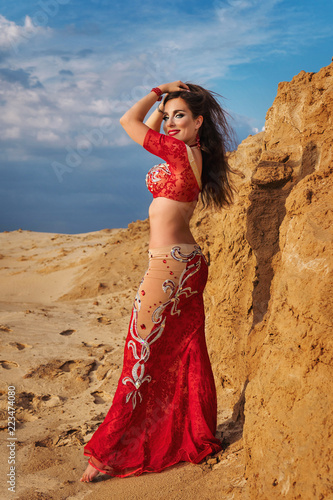 e5b86d52ac778 Oriental Beauty dancing sensual belly dance outdoors. Arab dance of  seduction. A girl in a red dress is straightening her hair. Full-length  portrait