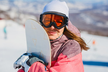 a young woman in glasses with orange ski snowboard