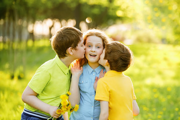 Little boys give his girl friend bouqet of yellow dandelions,