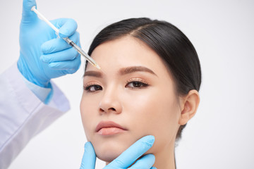 Young Vietnamese woman getting botox injection between her eyebrows