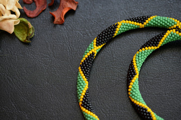 Bead crochet necklace in Jamaican style on a dark background close up