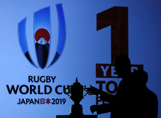 An official reaches out to the Webb Ellis Cup during a kick-off event to mark one year to go to the Rugby World Cup 2019, in Tokyo