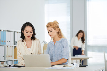 Serious pretty mixed-race coworkers reading data on laptop screen