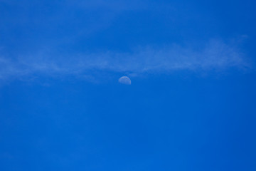 Half moon on blue sky and clouds